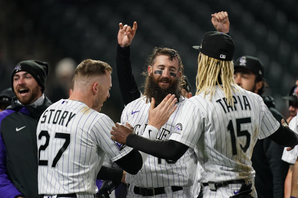 Colorado Rockies' Charlie Blackmon, center, is congratulated by Trevor Story (27) and Raimel Tapia (15) after Blackmon hit a three-run, walkoff home run off San Francisco Giants relief pitcher Camilo Doval in the seventh inning of game two of a baseball doubleheader Tuesday, May 4, 2021, in Denver. The Rockies won the nightcap by score of 8-6.(AP Photo/David Zalubowski)