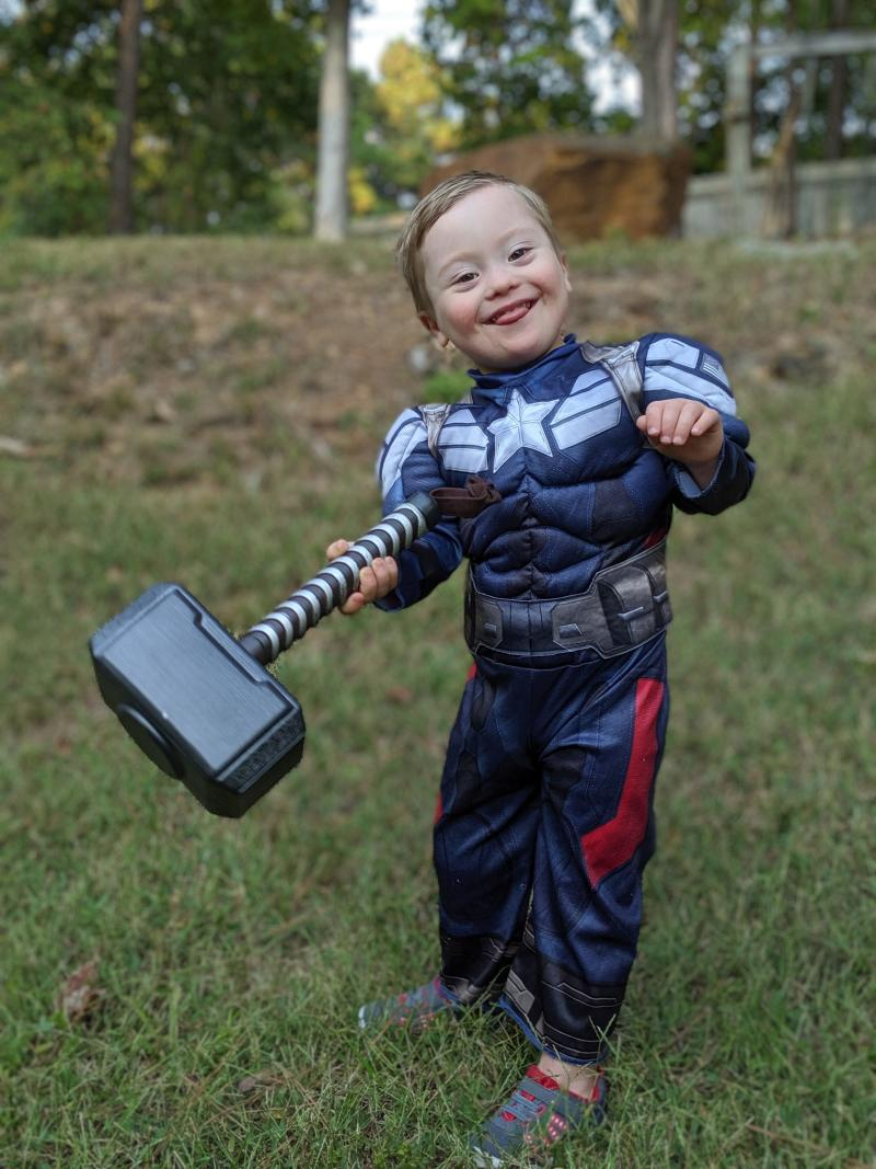 Adam's son who has Down syndrome dressed as Captain America holding Thor's hammer.