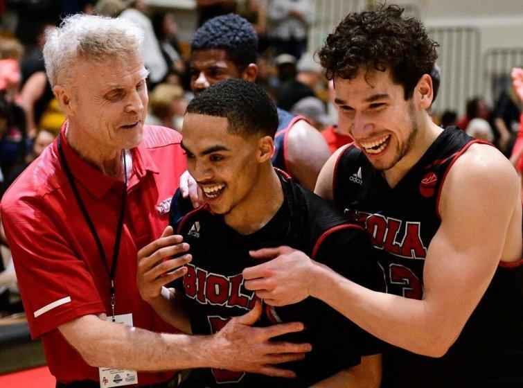 Biola University coach Dave Holmquist celebrates with players during a game.