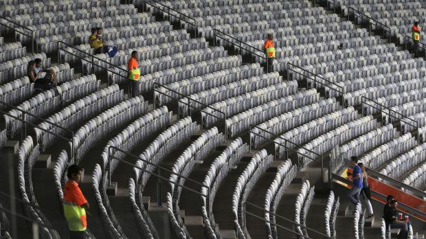 Stadium seats with only a few people sitting in them