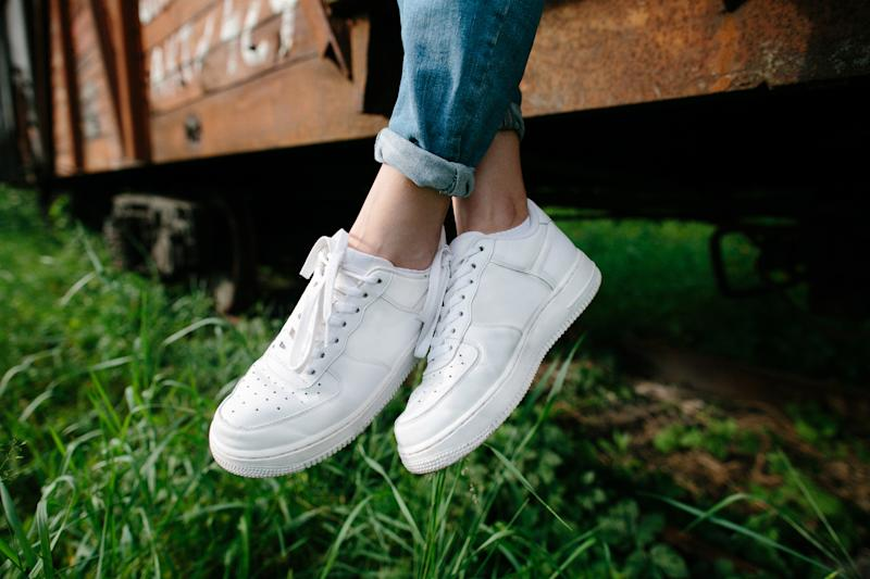 A photo of a female wearing jeans and white sneakers.
