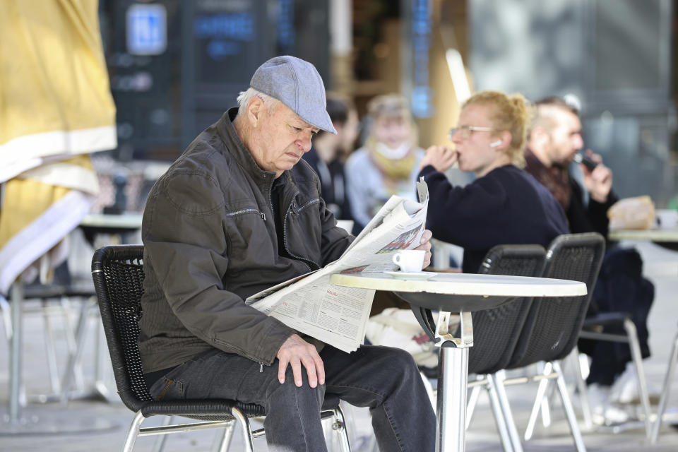 """A man reads a newspaper while seated in a cafe terrace, in Rennes, western France, Wednesday, May, 19, 2021. It's a grand day for the French. Cafe and restaurant terraces are reopening Wednesday after a pandemic shutdown of more than six months deprived people of what feels like the essence of life in France. The French government is lifting restrictions incrementally to stave off a resurgence of COVID-19 and to give citizens back some of their signature """"joie de vivre."""" (AP Photo/David Vincent)"""