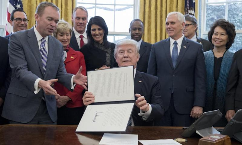 President Donald Trump signs an executive order in the Oval Office.