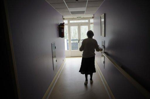 A woman, suffering from Alzheimer's desease, walks down a corridor in a retirement house in Angervilliers, eastern France. More than 100 years after it was first caught in the act of decaying a patient's brain, Alzheimer's remains one of medicine's greatest challenges as it robs ever more people of their memory and independence
