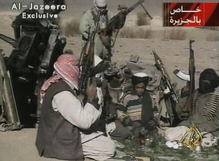 FILE - In this Nov. 5, 2001 image made from video broadcast by the Qatari-based television station Al-Jazeera, a young boy, center, identified as Hamza bin Laden, reads a poem about Taliban leader Mullah Mohammad Omar in Ghazni, Afghanistan. Years after the death of his father at the hands of a U.S. Navy SEAL raid in Pakistan, it is now Hamza bin Laden who finds himself squarely in the crosshairs of world powers. In rapid succession in recent weeks, the U.S. put a bounty of up to a $1 million for him; the U.N. Security Council named him to a global sanctions list, sparking a new Interpol notice for his arrest; and his home country of Saudi Arabia revealed it had revoked his citizenship. (AP Photo/Al-Jazeera via APTN, File)