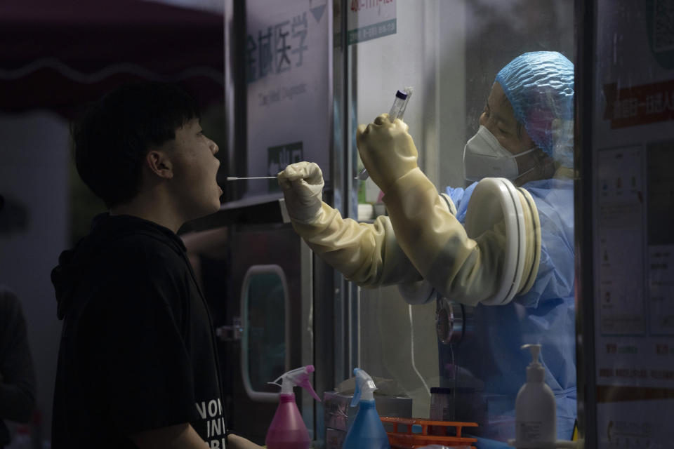 """A man gets swapped during a nuclei test for COVID-19 in Beijing Saturday, Sept. 18, 2021. China's """"zero tolerance"""" strategy of trying to isolate every case and stop transmission of the coronavirus has kept kept the country where the virus first was detected in late 2019 largely free of the disease. (AP Photo/Ng Han Guan)"""