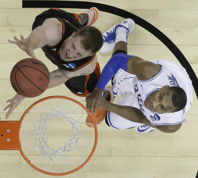 Mercer forward Jakob Gollon (20) shoots over Duke forward Jabari Parker (1) during the first half of an NCAA college basketball second-round game, Friday, March 21, 2014, in Raleigh, N.C. (AP Photo/Chuck Burton)