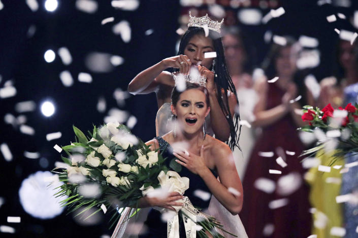 FILE - In this Dec. 19, 2019, file photo, Camille Schrier, of Virginia, reacts as she is crowned by 2019 Miss America Nia Franklin after winning the Miss America competition at the Mohegan Sun casino in Uncasville, Conn. The 100th Miss America will be crowned before a live audience at the Mohegan Sun casino in Connecticut following a year of virtual appearances and postponed competitions due to the pandemic, organizers announced Thursday, April 8, 2021. (AP Photo/Charles Krupa, File)
