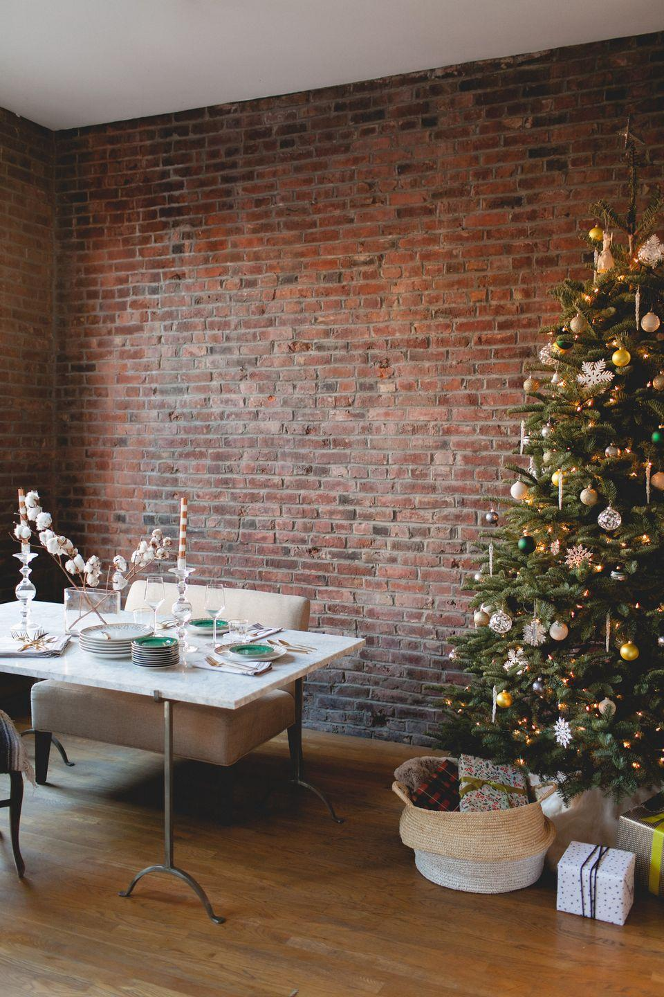 "<p>What's the perfect addition to an exposed-brick dining room? A beautifully designed Christmas tree, naturally. This city loft gets a magical touch of the forest with a tree daintily designed by <a href=""http://www.cocokelley.com/2014/12/merry-christmas/"" rel=""nofollow noopener"" target=""_blank"" data-ylk=""slk:Coco Kelley"" class=""link rapid-noclick-resp"">Coco Kelley</a> in yellow, green, and silver ornaments—and, of course, cushioned with presents. </p>"