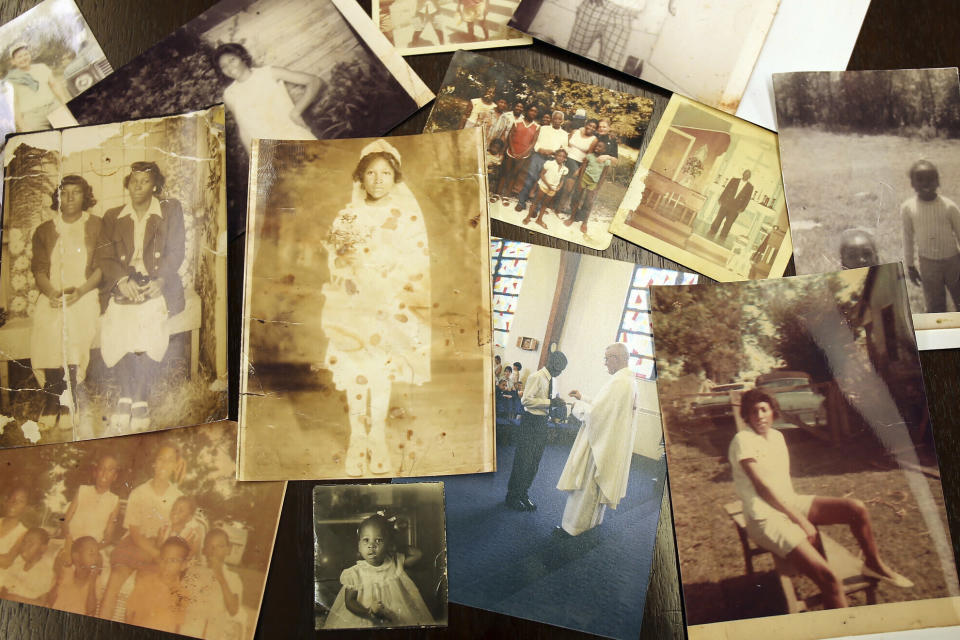 """FILE - This April 24, 2019 photo shows photographs of descendants of enslaved people who were sold by Georgetown University and the Maryland Jesuits to southern Louisiana in 1838. In March 2021, the U.S.-based branch of the Jesuits has unveiled ambitious plans for a """"truth and reconciliation"""" initiative in partnership with descendants of slaves once owned by the religious order. The Jesuits pledge to raise $100 million within five years; the broader goal is to raise $1 billion from an array of donors in pursuit of racial justice and racial healing. (Claire Vail/American Ancestors/New England Historic Genealogical Society via AP)"""