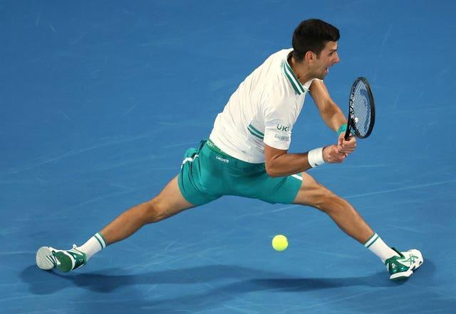 Novak Djokovic stretches to hit a backhand behind his back