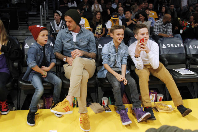 British soccer player David Beckham (2nd L) sits courtside with his sons Cruz (L), Romeo (2nd R) and Brooklyn (R) before the NBA basketball game between the Los Angeles Lakers and Phoenix Suns in Los Angeles November 16, 2012. REUTERS/Danny Moloshok (UNITED STATES - Tags: SPORT BASKETBALL ENTERTAINMENT SOCCER)