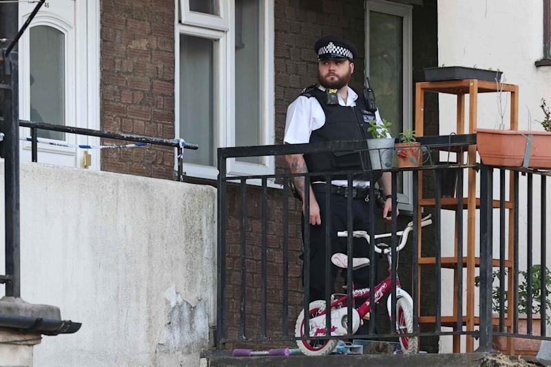 Horror: a police officer stands guard outside the flat in Mitcham today (Evening Standard / eyevine)