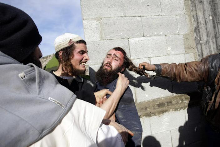 """FILE - In this file photo taken Tuesday, Jan. 7, 2014, Palestinians hit injured Israeli settlers, center, detained by Palestinian villagers in a building under construction near the West Bank village of Qusra, southeast of Nablus. The annual rate of Israeli settler attacks against Palestinians has almost quadrupled in eight years, U.N. figures show, buttressing claims that Israeli security forces have largely failed to stem the so-called """"price tag"""" campaign in which thugs cut down trees, deface mosques and beat Palestinian farmers. (AP Photo/Nasser Ishtayeh, File)"""