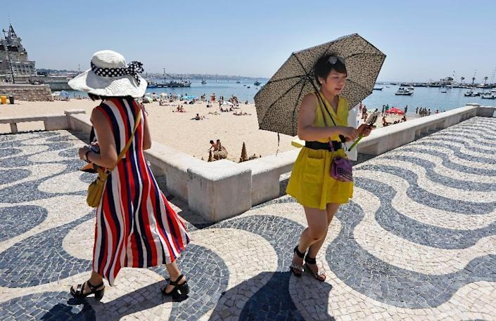 A tourist uses an umbrella to protect from the sun as she goes for a walk on the outskirts of Lisbon on June 29, 2015 (AFP Photo/Jose Manuel Ribeiro)