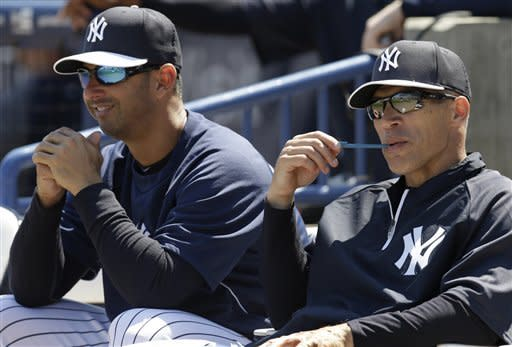 Former New York Yankees catcher Jorge Posada, left, sits beside Yankees manager Joe Girardi during a spring training baseball game against the Miami Marlins in Tampa, Fla., Friday, March 15, 2013. Posada is in camp as a guest instructor for several days. (AP Photo/Kathy Willens)