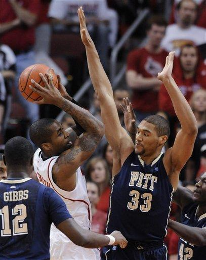 Louisville's Chris Smith looks for help as Pittsburgh's Ashton Gibbs, left, and Malcolm Gilbert defend during the first half of an NCAA college basketball game Sunday, Feb. 26, 2012, in Louisville, Ky. (AP Photo/Timothy D. Easley)