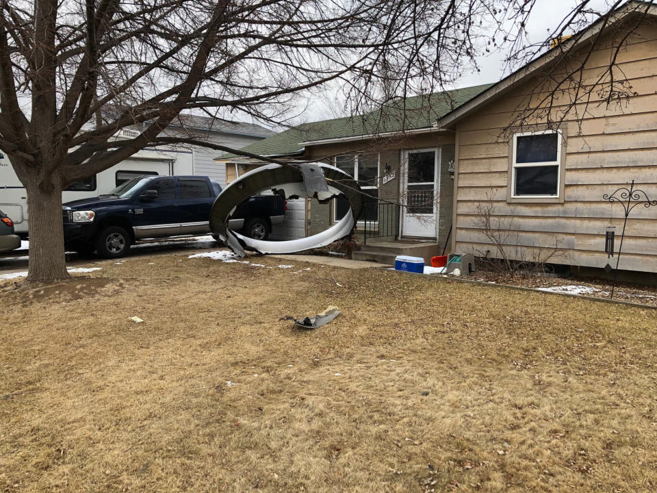 In this photo provided by the Broomfield Police Department on Twitter, debris is scattered in the front yard of a house at near 13th and Elmwood, Saturday, Feb. 20, 2021, in Broomfield, Colo. A commercial airliner dropped debris in Colorado neighborhoods during an emergency landing Saturday. The Broomfield Police Department said on Twitter that the plane landed safely at Denver International Airport and that no injuries had been reported from the incident. (Broomfield Police Department via AP)