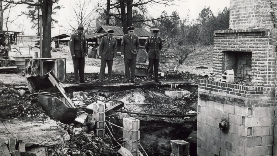 Four of Vernon Dahmer's sons, dressed in their military uniforms, view their family home after it was firebombed on Jan. 10, 1966. (Chris McNair via Lisa McNair)