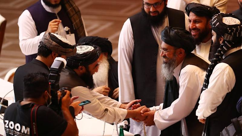 Taliban delegates shake hands during talks between the Afghan government and Taliban insurgents in Doha, Qatar September 12, 2020