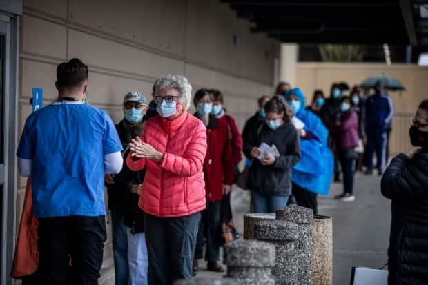 People are pictured lined up to receive their COVID-19 vaccination at an immunization clinic in the Fraser Health region of Surrey, B.C., on March 24, 2021. (Ben Nelms/CBC - image credit)