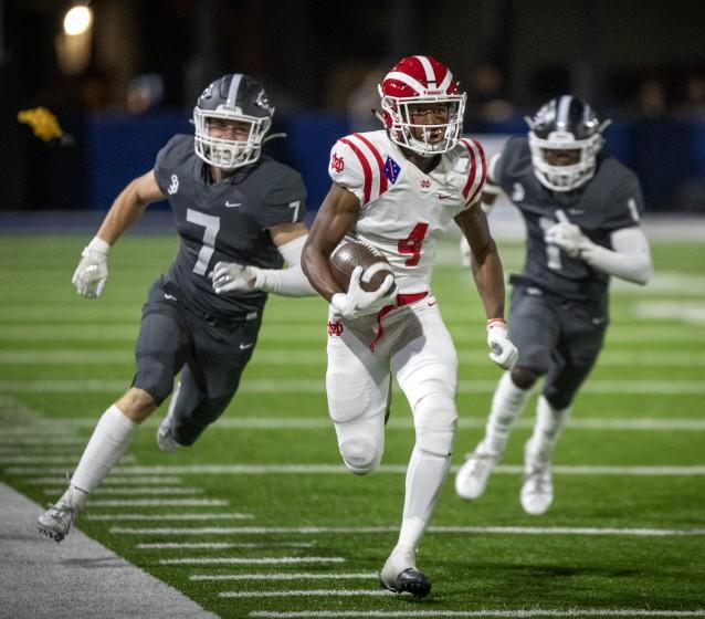 """St. John Bosco's Jake Newman, left, and Josh Alford pursue Mater Dei receiver Kody Epps in Bellflower, Calif., on Oct. 25, 2019. The 2020 high school sports season will be delayed. <span class=""""copyright"""">(Allen J. Schaben / Los Angeles Times)</span>"""