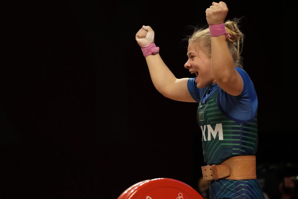 Polina Guryeva of Turkmekistan celebrates after the last lift as she competes in the women's 59kg weightlifting event, at the 2020 Summer Olympics, Tuesday, July 27, 2021, in Tokyo, Japan. (AP Photo/Luca Bruno)