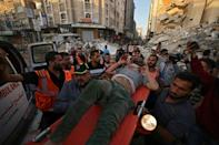 Palestinians carry a survivor of an Israeli strike in Gaza to an ambulance