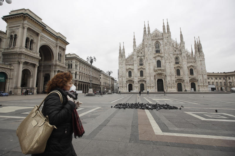 A woman crosses the empty Duomo Square in downtown Milan, Italy Thursday, March 12, 2020. The outbreak of the coronavirus has led to a nationwide lockdown in Italy as the government is seeking to slow down its spread. For most people, the new coronavirus causes only mild or moderate symptoms, such as fever and cough. For some, especially older adults and people with existing health problems, it can cause more severe illness, including pneumonia. (AP Photo/Luca Bruno)