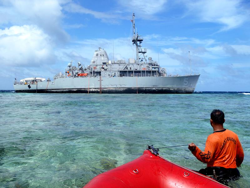 In this Jan. 22, 2013 photo released by the Philippine Coast Guard, coast guard divers approach the USS Guardian, a U.S. Navy minesweeper, to assess the situation after it ran aground last week off Tubbataha Reef, a World Heritage Site in the Sulu Sea, 640 kilometers (400 miles) southwest of Manila, Philippines. A U.S. Navy official said the USS Guardian has been punctured and taking in water and has to be lifted off the rocks. (AP Photo/Philippine Coast Guard) EDITORIAL USE ONLY, NO SALES