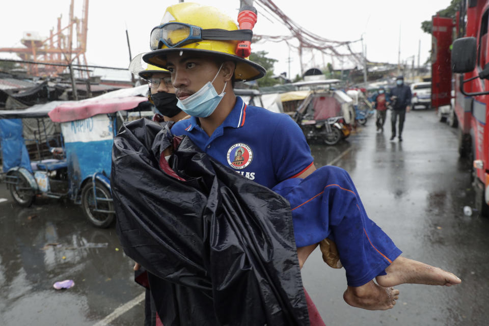 A rescuer carries a sick child as they evacuate residents living along a coastal community in Manila, Philippines on Sunday, Nov. 1, 2020. A super typhoon slammed into the eastern Philippines with ferocious winds early Sunday and about a million people have been evacuated in its projected path, including in the capital where the main international airport was ordered closed. (AP Photo/Aaron Favila)