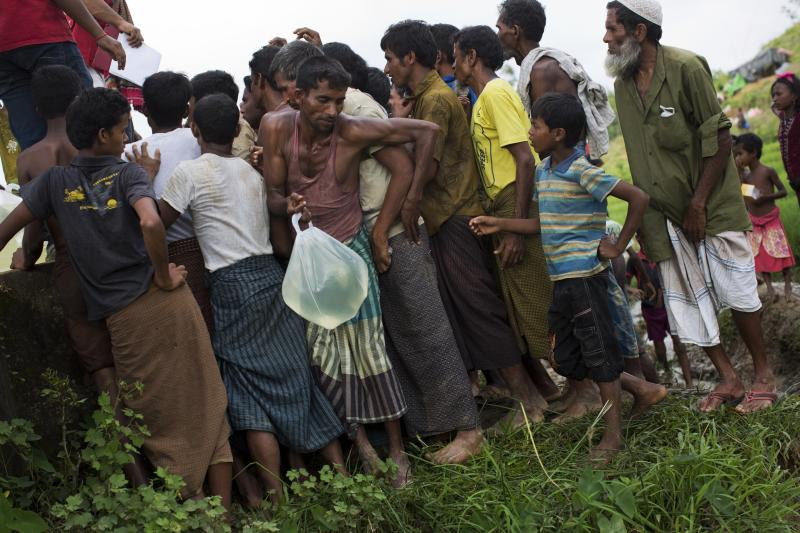 In this Sept. 4, 2017 file photo, Rohingya Muslims living in no man's land collect water donated by Bangladesh Red Crescent members, near Cox's Bazar's Tombru area. Some 6,000 Rohingya Muslim refugees who fled attacks in Myanmar last year live at the cloudiest edges of the border with Bangladesh, in a no man's land that seems to be neither Myanmar nor Bangladesh. Many stay in these places because they are from nearby villages, and can see the wreckage of their former homes. But the Myanmar government insists no man's land doesn't exist, and the 6,000 refugees are living inside Myanmar. (AP Photo/Bernat Armangue, File)