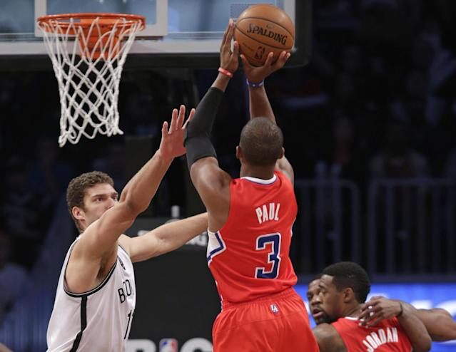 Los Angeles Clippers guard Chris Paul (3) shoots over Brooklyn Nets center Brook Lopez (11) in the first half of their NBA basketball game at the Barclays Center, Thursday, Dec. 12, 2013, in New York. (AP Photo/Kathy Willens)