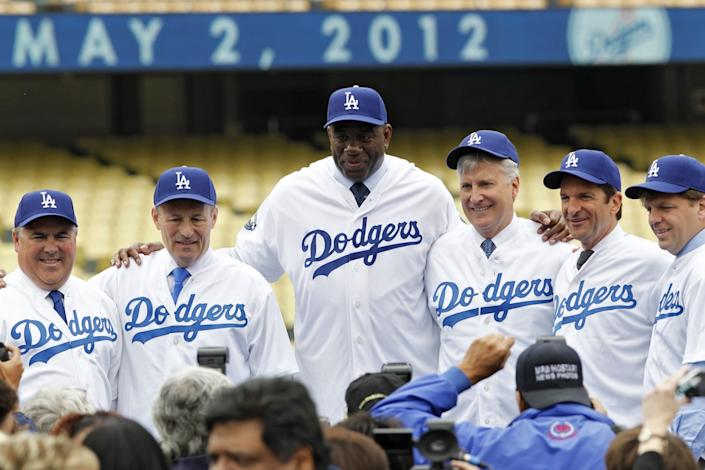 Dodgers owners, including Lakers legend Magic Johnson, center, pose for photos.
