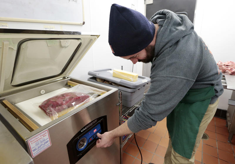 """In this Dec. 11, 2013 photo, James Peisker vacuum-seals a bag containing a beef top round and a marinade as part of the process of preparing the """"spiced round,"""" a Christmastime beef specialty, at the Porter Road Butcher in Nashville, Tenn. The beef will marinate for six days. (AP Photo/Mark Humphrey)"""