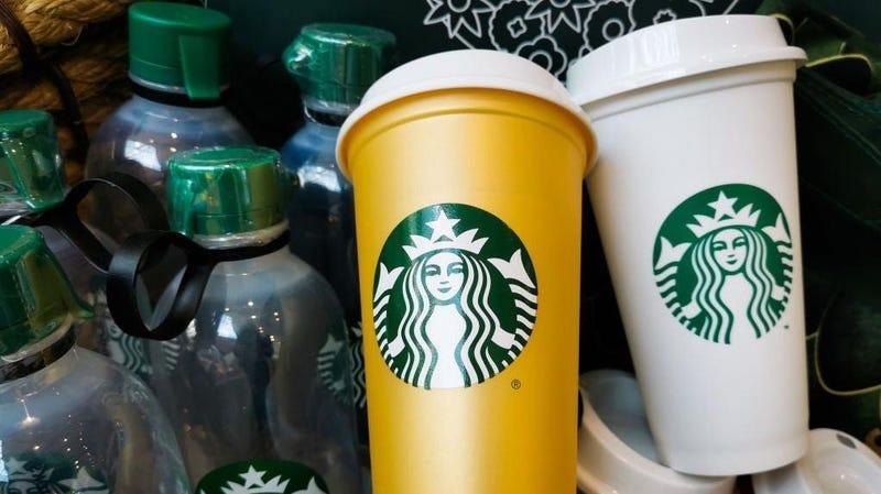 Orange and white reusable cups featuring Starbucks logo