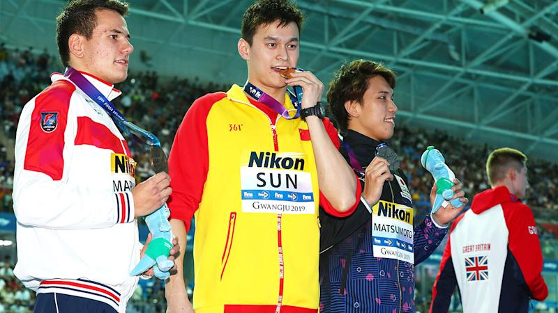 Martin Malyutin, Sun Yang and Katsuhiro Matsumoto pose with their medals from the 200m final as Duncan Scott walks away. (Photo by Clive Rose/Getty Images)