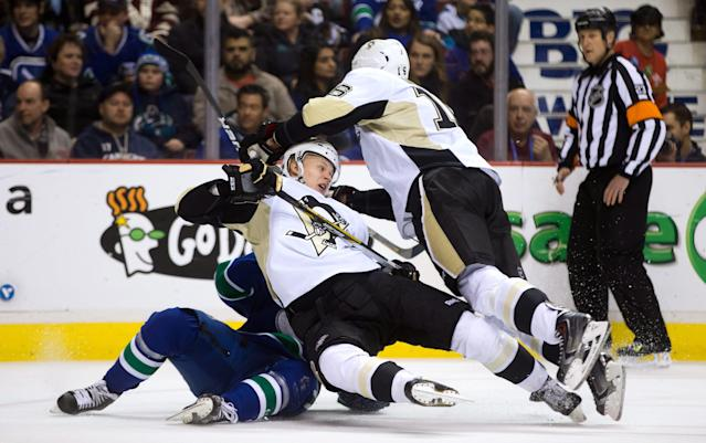 Pittsburgh Penguins' Olli Maatta, center, of Finland, and Brandon Sutter, right, and Vancouver Canucks' Jannik Hansen, left, of Denmark, collide during the first period of an NHL hockey game Tuesday, Jan. 7, 2014, in Vancouver, British Columbia. (AP Photo/The Canadian Press, Darryl Dyck)
