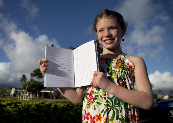 """Kyrstin Lavelle, 10, holds open her book for photographers to see with President Barack Obama's autograph and comment that reads """"To Kyrstin Dream Big Deams"""" on Marine Corps Base Hawaii in Kaneohe, Hawaii, Tuesday, Dec. 24, 2013. Kyrstin and her family met President Obama outside the base workout facility as he entered. The first family is in Hawaii for their annual holiday vacation. (AP Photo/Carolyn Kaster)"""