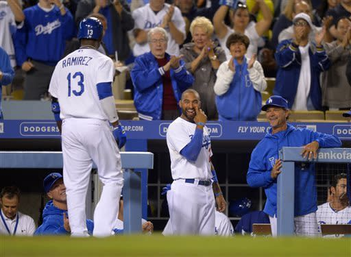 Los Angeles Dodgers' Hanley Ramirez, left, walks into the dugout as Matt Kemp, center and manager Don Mattingly smile after hitting a solo home run during the third inning of their baseball game against the Colorado Rockies, Tuesday, April 30, 2013, in Los Angeles. (AP Photo/Mark J. Terrill)