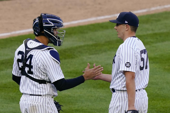 New York Yankees relief pitcher Chad Green (57) and catcher Gary Sanchez (24) celebrate after closing the ninth inning of a baseball game against the Toronto Blue Jays, Saturday, April 3, 2021, in New York. (AP Photo/John Minchillo)
