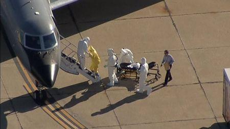 Texas nurse Amber Vinson is helped up the steps of a waiting aircraft by personnel in this still image taken from video courtesy of NBC5- KXAS in Dallas, Texas October 15, 2014. REUTERS/NBC5-KXAS TV