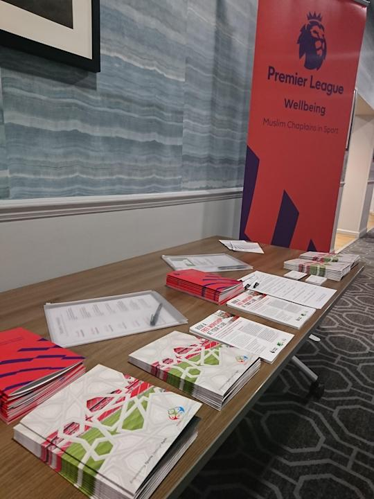 A picture of some leaflets and literature from the Muslim Chaplains In Sport, on a light brown table with an orange Premier League sign next to it that reads 'Premier League Wellbeing - Muslim Chaplains in Sport'