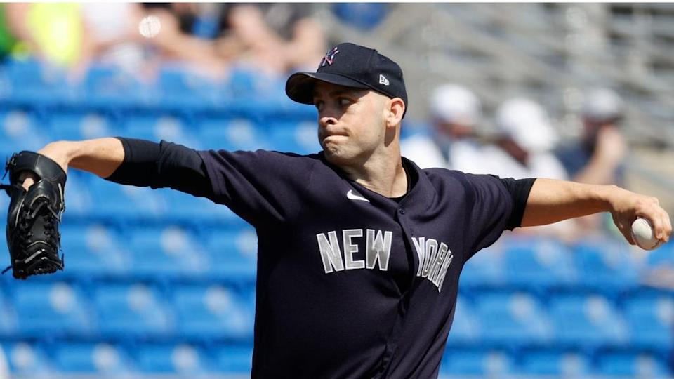 Lucas Luetge fires pitch to home in Yankees navy blue spring jersey
