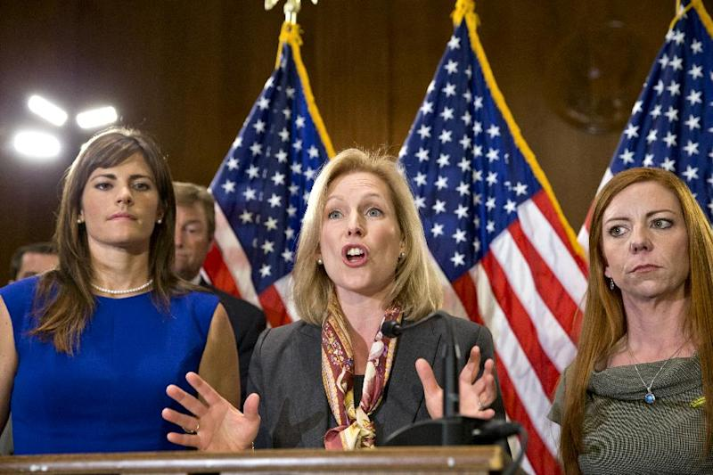 Sen. Kirsten Gillibrand, D-N.Y., center, flanked by Sarah Plummer, a Marine Corps veteran who was a victim of sexual assault, left, and Kate Weber, a veteran who was sexually assaulted during her service in the Army, gestures while speaking at a news conference on Capitol Hill in Washington, Tuesday, Nov. 19, 2013. They are joined by supporters of her proposal to let military prosecutors rather than commanders make decisions on whether to prosecute sexual assaults in the armed forces. (AP Photo/J. Scott Applewhite)