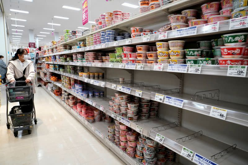 FILE PHOTO: A shopper wearing a protective mask looks at shelves at a supermarket in Tokyo