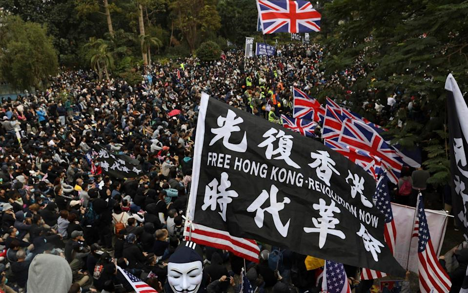 Hong Kong protesters wave British and US flags during a rally protesting against Beijing's new national security law earlier this year - Ng Han Guan/AP Photo