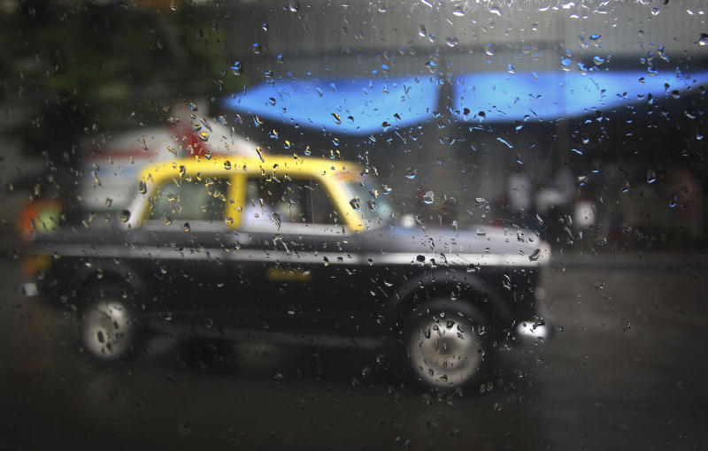 In this Tuesday, July 30, 2013, a Mumbai's Premier Padmini taxi is seen as rain droplets gather on the window of another taxi in Mumbai, India. More than 4500 Premier Padmini taxis are expected to be banned from the roads in Mumbai this year, starting in August, in line with a government order that bans cabs that are more than 20 years old. (AP Photo/Rafiq Maqbool)