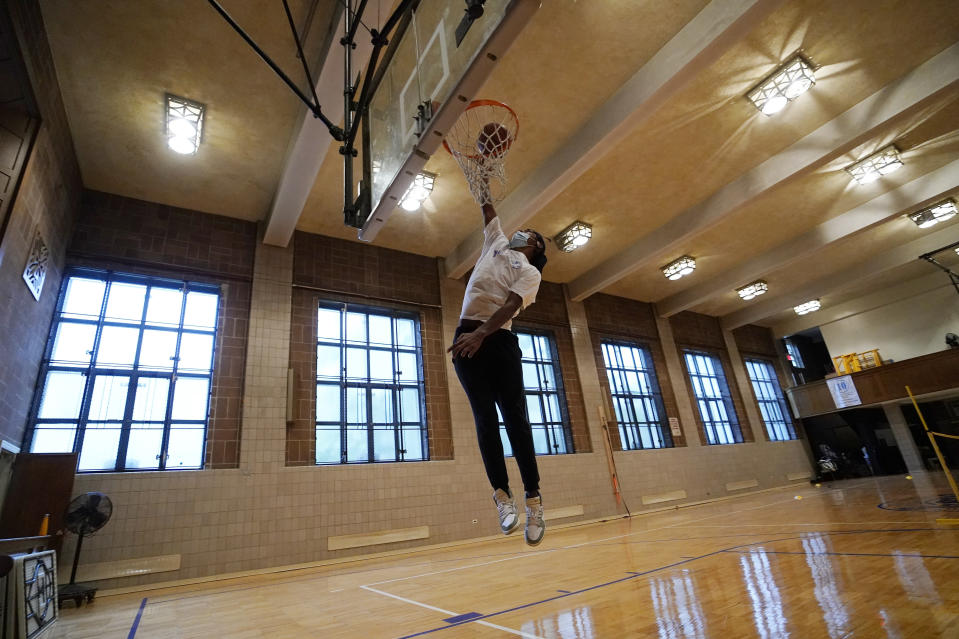 """Kenny Scottborough, 19, goes up for a shot in an empty gymnasium at West Brooklyn Community High School, Thursday, Oct. 29, 2020, in New York. The high school is a """"transfer school,"""" catering to a students who haven't done well elsewhere, giving them a chance to graduate and succeed. Good Shepherd Services provides advocate counselors to help West Brooklyn's students achieve their goals. (AP Photo/Kathy Willens)"""
