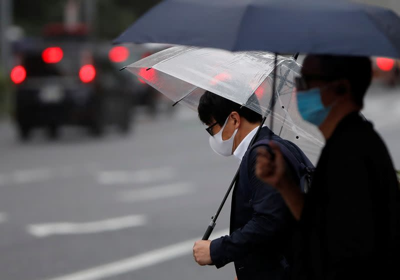 Passersby wearing protective face masks are seen on the street amid the coronavirus disease (COVID-19) outbreak, in Tokyo